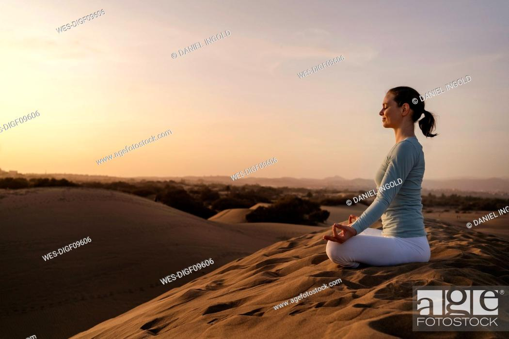 Stock Photo: Woman practicing yoga in sand dunes at sunset, Gran Canaria, Spain.