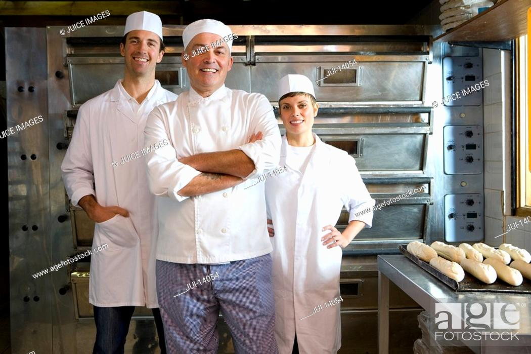 Stock Photo: Bakers by tray of baguettes, smiling, portrait.