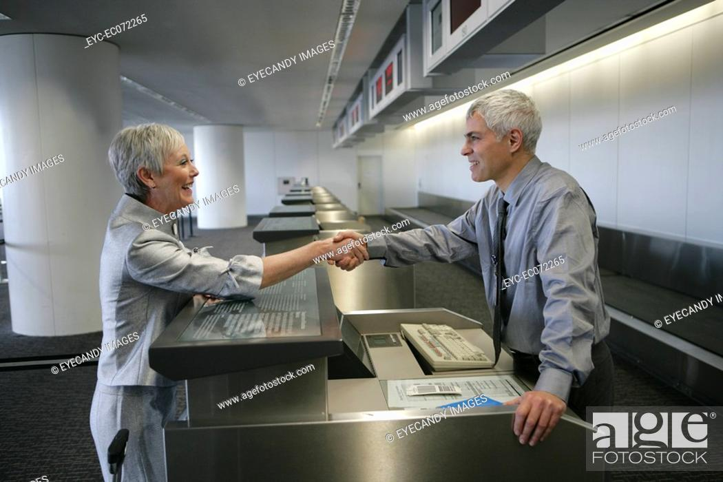Stock Photo: Check in attendant and passenger shaking hands at airport check in counter.
