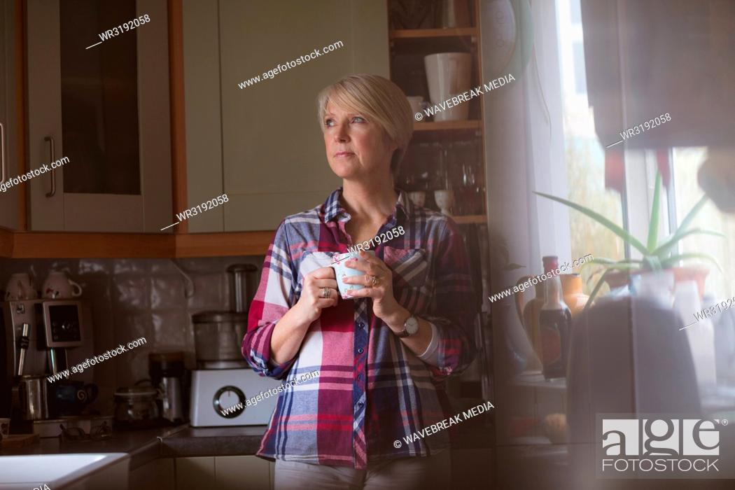 Stock Photo: Mature woman having coffee in kitchen.
