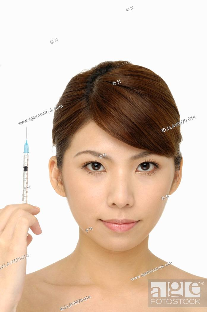 Stock Photo: young beautiful woman with syringe in her hand - white background.
