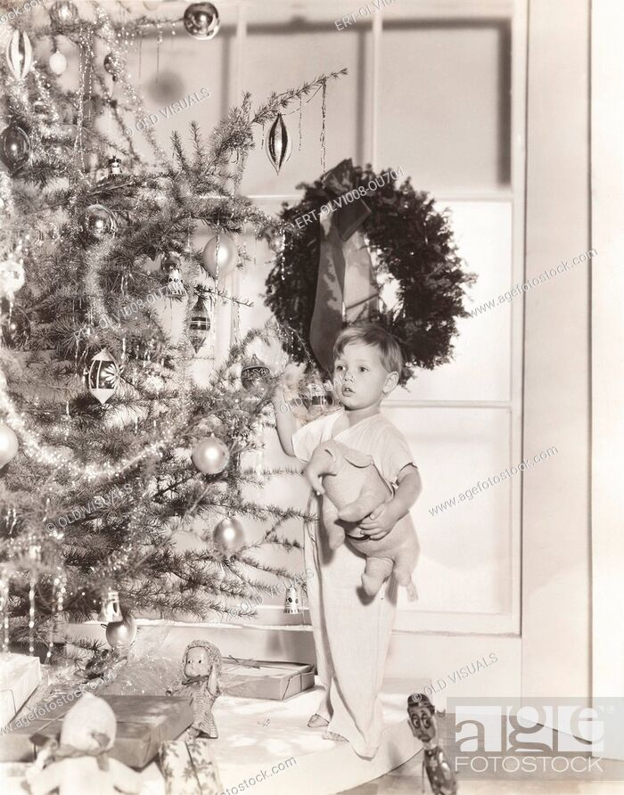 Stock Photo: Little boy standing by tree on Christmas morning.