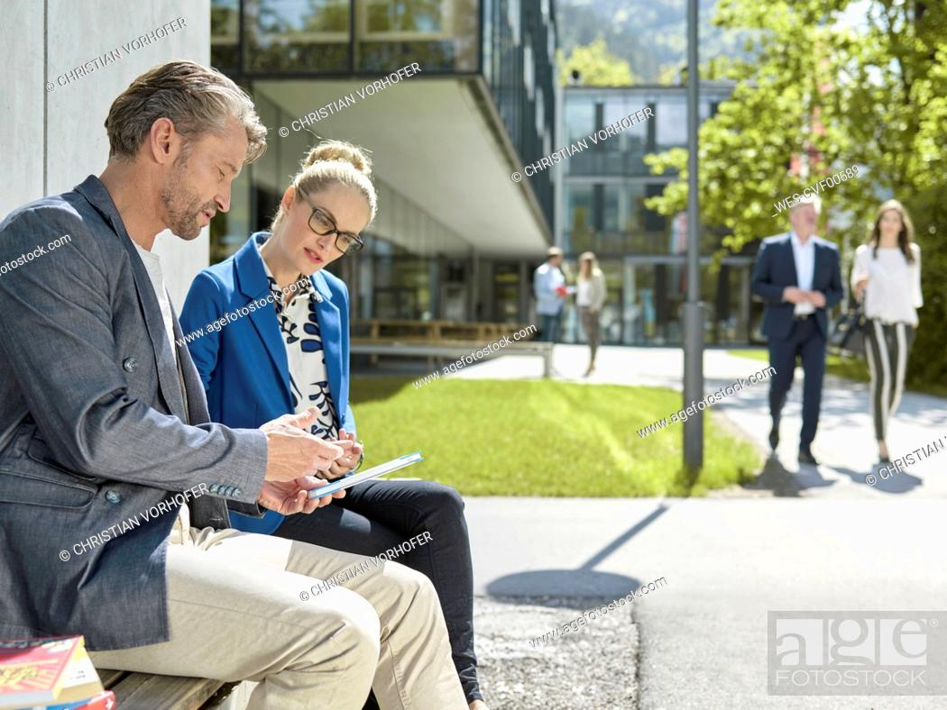 Stock Photo: Colleagues with tablet sitting on bench outside office building.