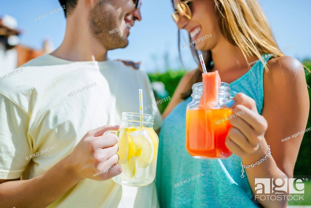 Photo de stock: Couple holding refreshing drinks outdoors.