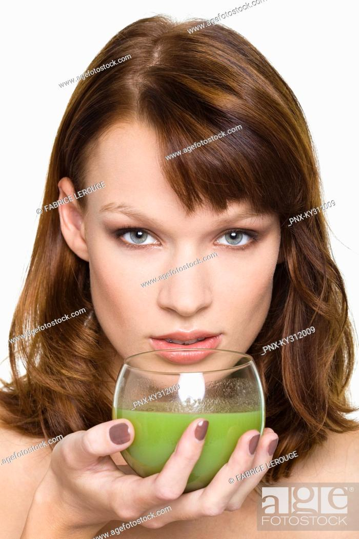 Stock Photo: Young woman holding glass of wheatgrass juice.