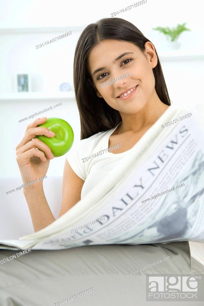 Stock Photo: Female sitting, holding apple and newspaper, smiling at camera.