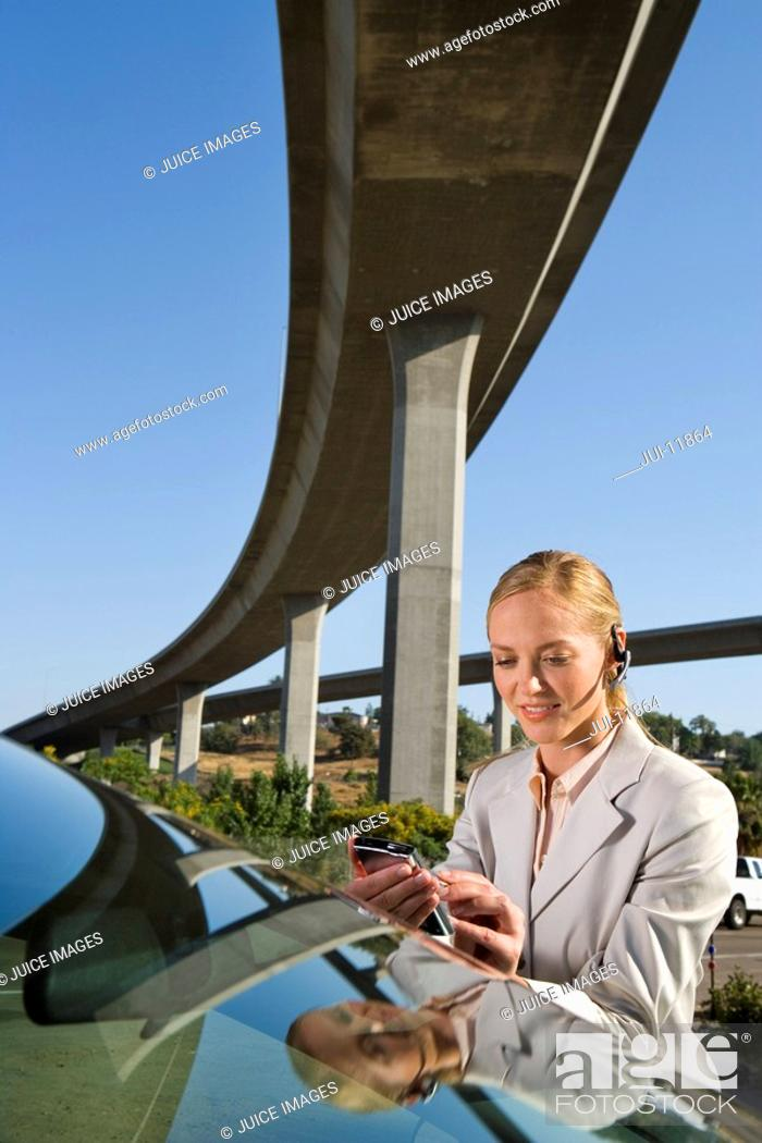 Stock Photo: Businesswoman with earpiece using electronic organiser by car beneath overpass.