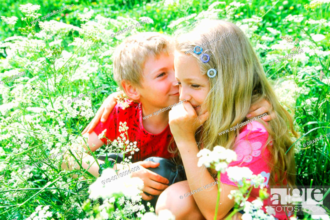 Stock Photo: Boy and girl sitting in the grass.