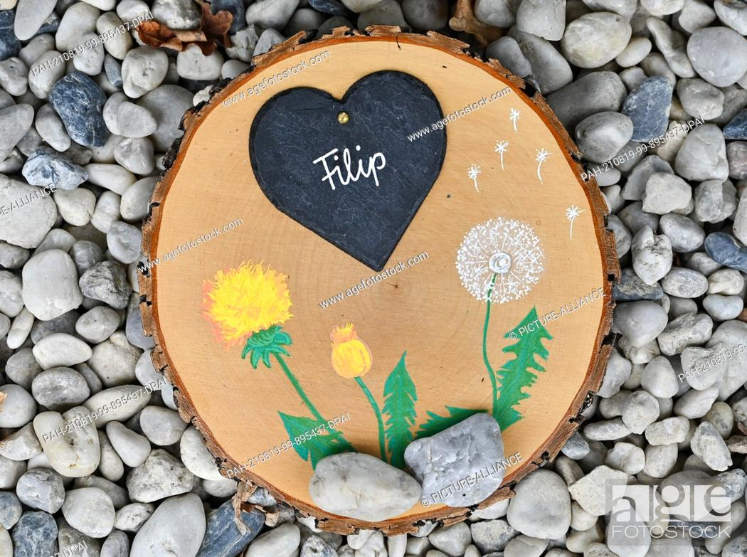 """Stock Photo: 19 August 2021, Brandenburg, Burg: A painted wooden memorial disc with a heart and the name """"""""Filip"""""""" can be seen at the children's hospice """"""""Pusteblume"""""""" run."""