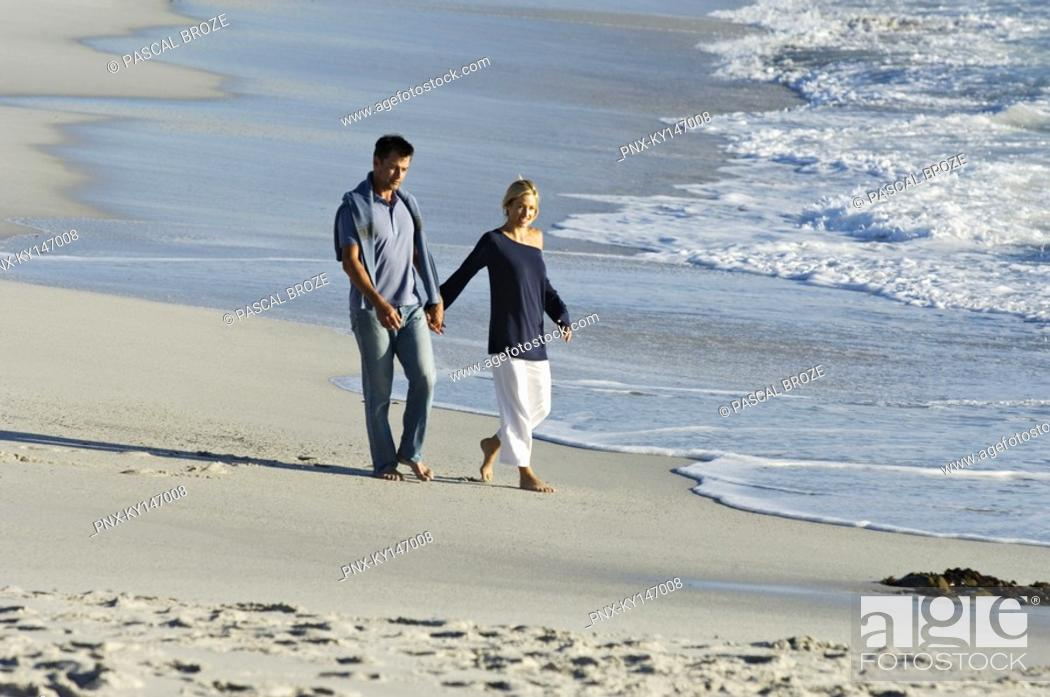 Stock Photo: Couple holding hands, walking on the beach.