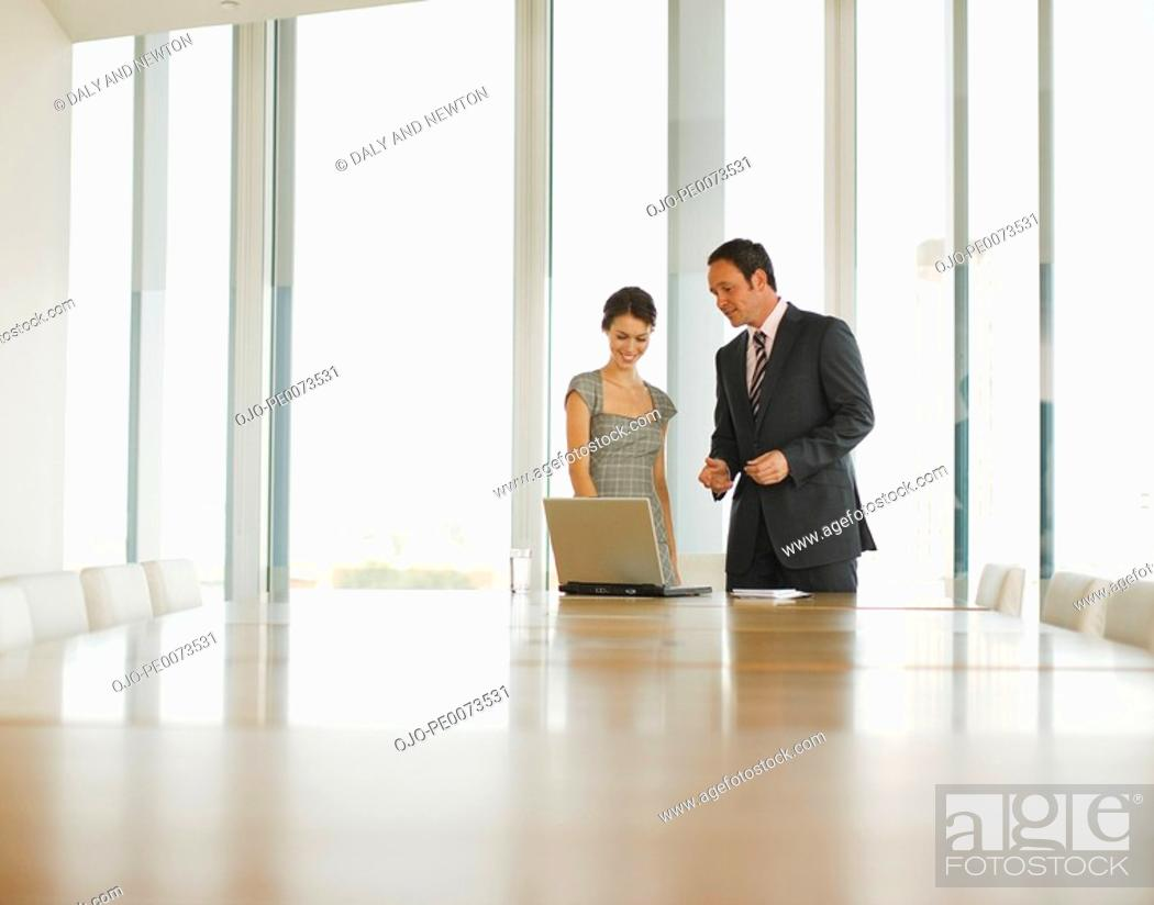 Stock Photo: Business people using laptop in conference room.
