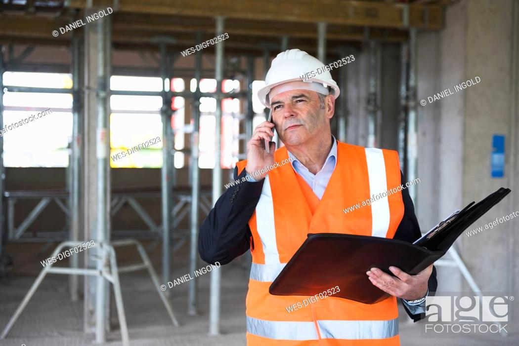 Stock Photo: Man on the phone wearing safety vest in building under construction.