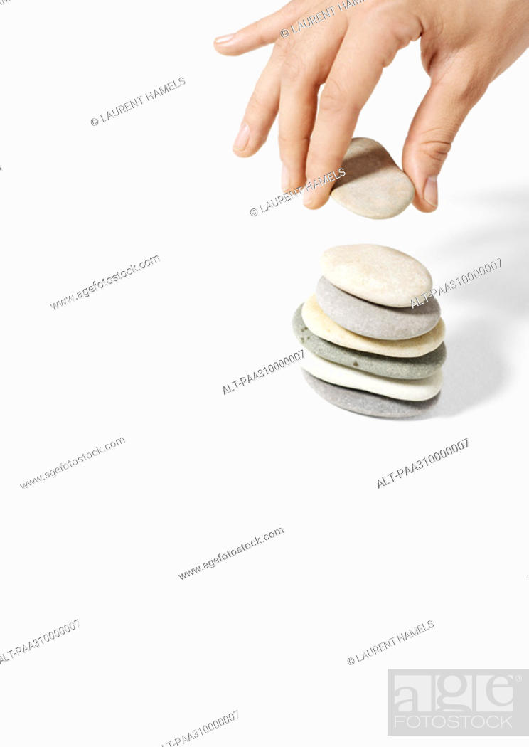 Stock Photo: Hand stacking pebbles.