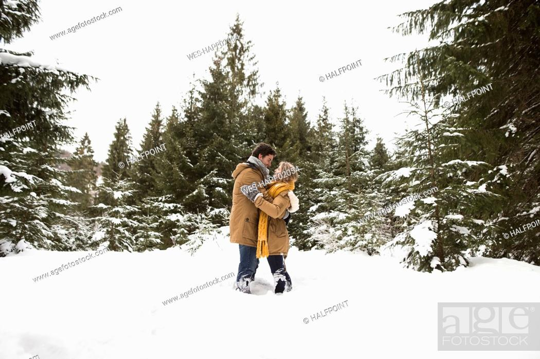 Stock Photo: Happy young couple standing face to face in winter landscape.