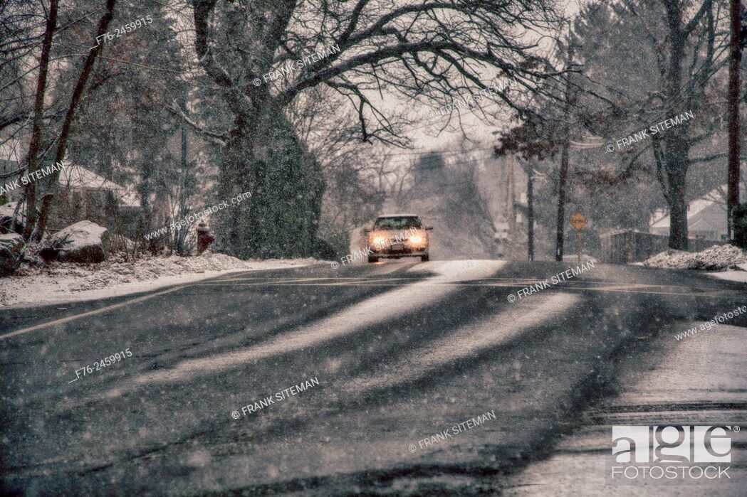 Stock Photo: lone care wiht headlights on at dusk, driving through snow storm on a suburban roadway in Winchester, MA.