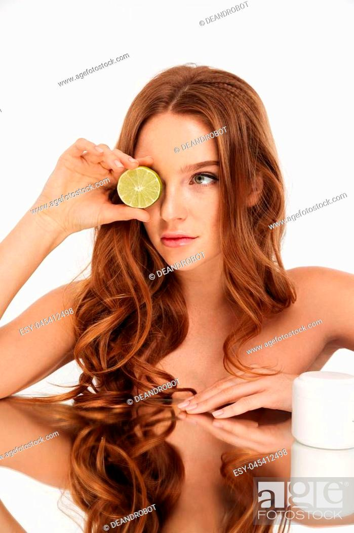 Stock Photo: Vertical Beauty portrait of ginger woman with long hair sitting by the mirror table with body cream and citrus over grey background.