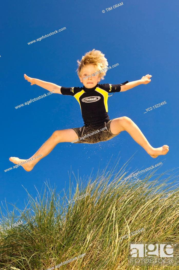 Stock Photo: A seven year old boy playing in the sand dunes at Wells-next-the-sea , Norfolk , England , Britain , Uk.