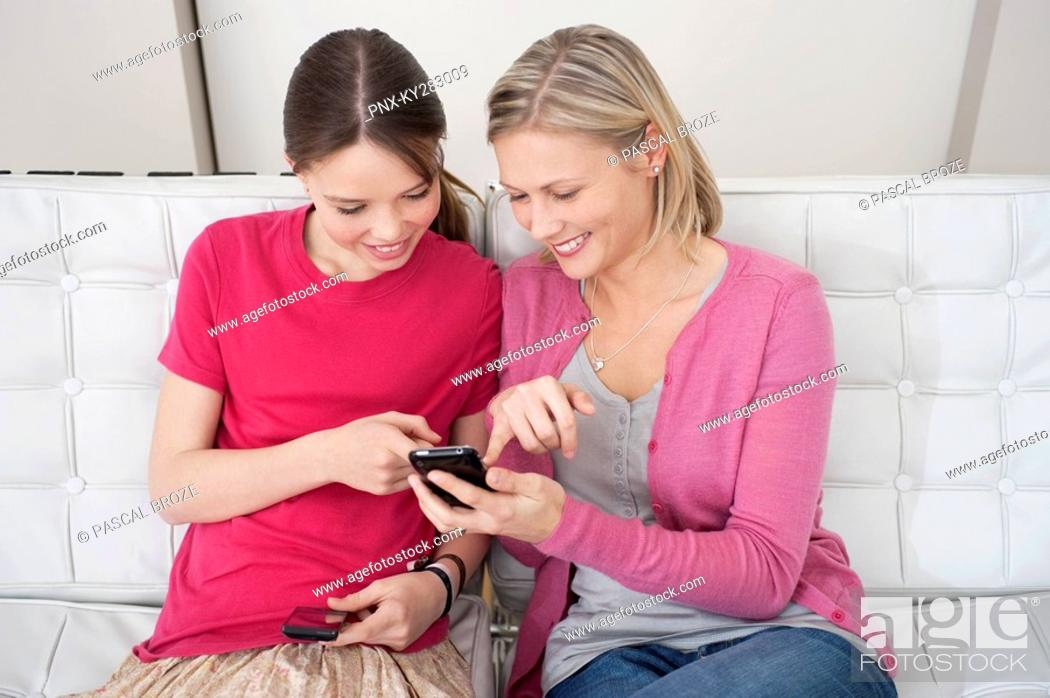 Stock Photo: Woman and her daughter reading a text message on a mobile phone.