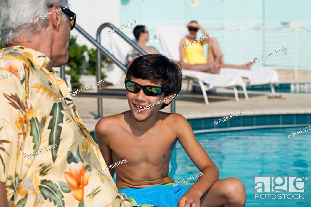 Stock Photo: Side profile of a senior man sitting with his grandson at poolside.