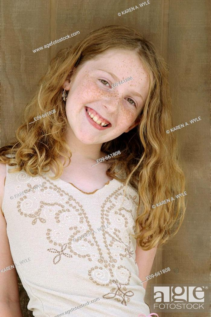 Stock Photo: Preteen girl with long gold-brown hair and freckles, smiling at camera, head tilted to side, waist up, against brown wood background.