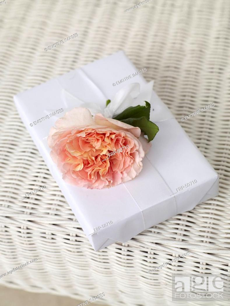 Stock Photo: White wrapped gift with a blossom.