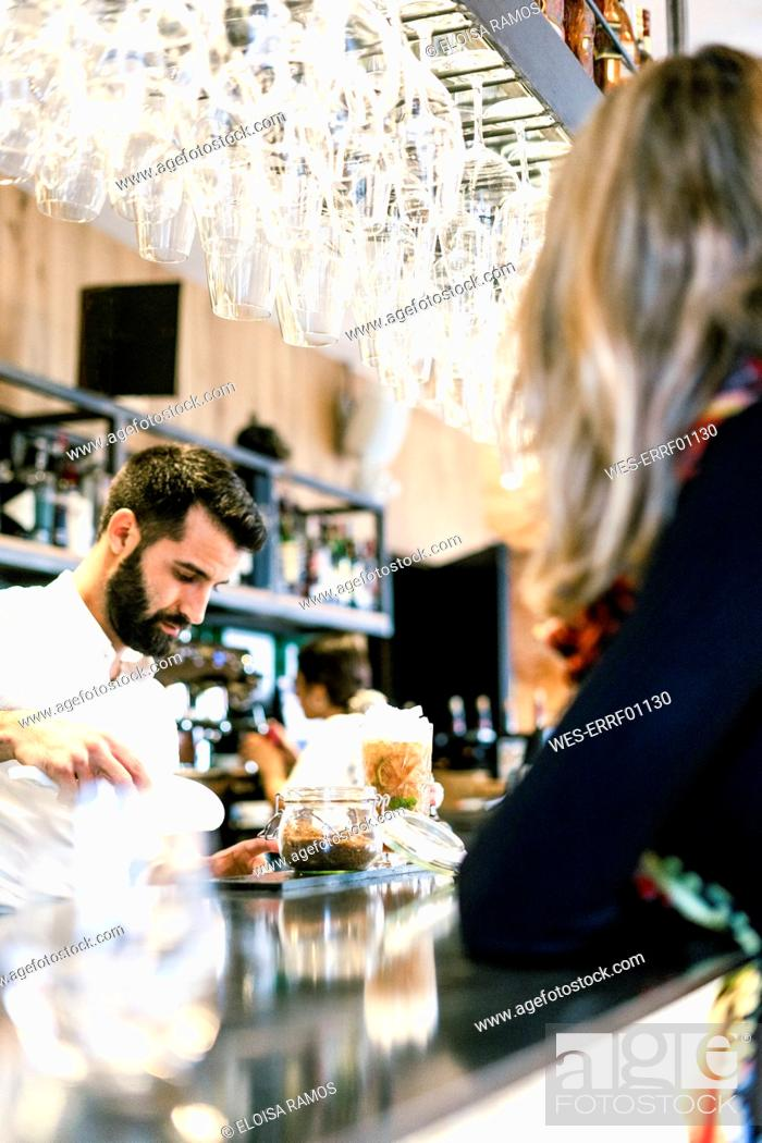 Stock Photo: Woman at the counter of a bar watching barkeeper preparing a cocktail.