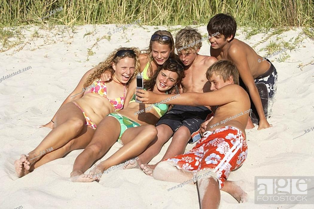 Stock Photo: Group of teenagers 13-15 lying on sandy beach, teenage boy taking photograph with camera, smiling.