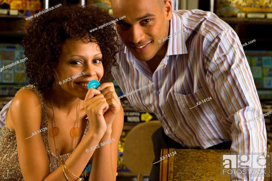 Stock Photo: Young couple gambling, woman with gambling chip, smiling, portrait.