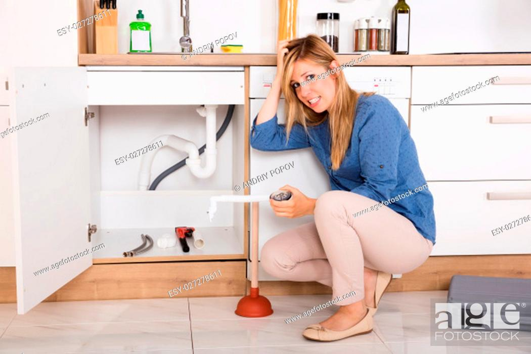 Stock Photo: Young Frustrated Woman Having Sink Problem Trying To Fix Sewer Drainage In Kitchen.