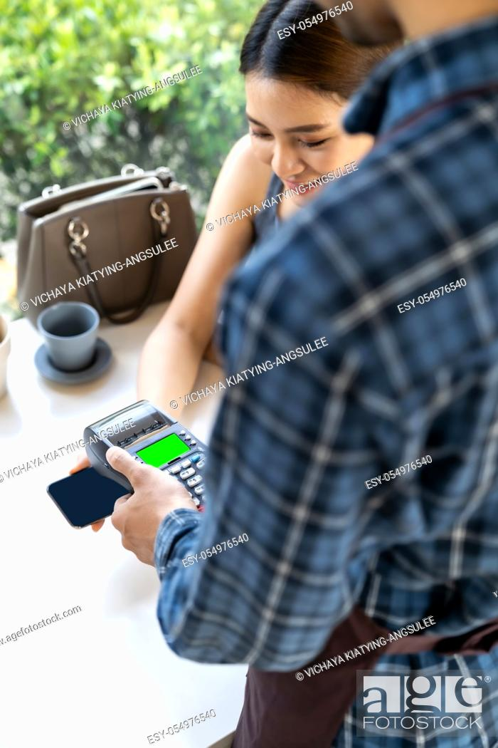 Stock Photo: Asian woman customer moblie phone to make online contactless mobile payment after eating out in new normal social distance restaurant.