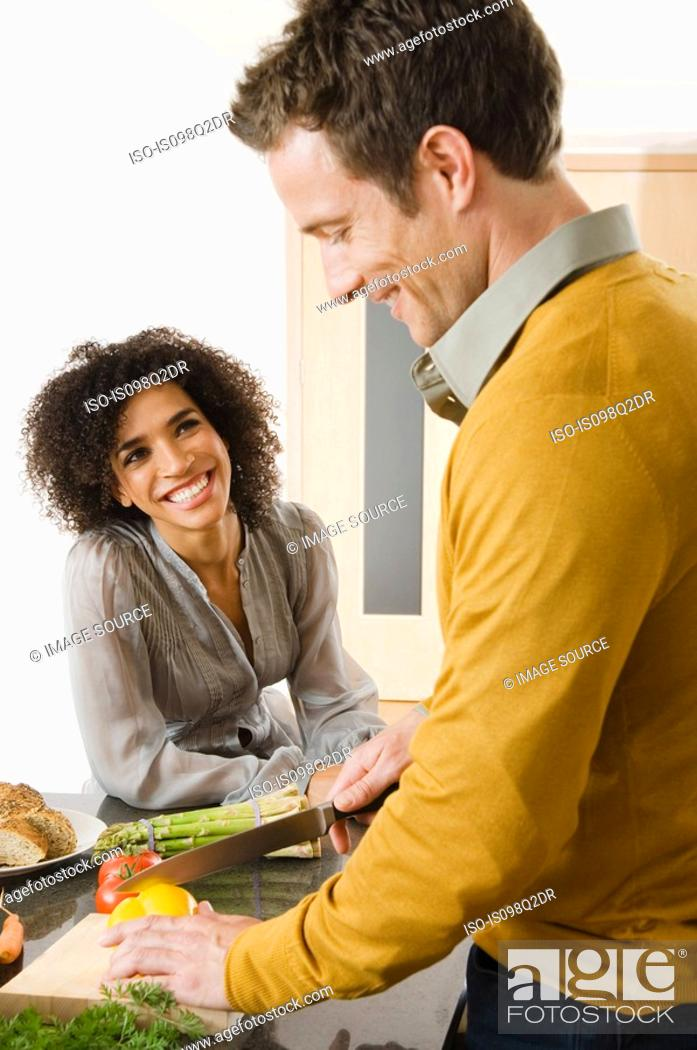 Stock Photo: A couple preparing food in a kitchen.