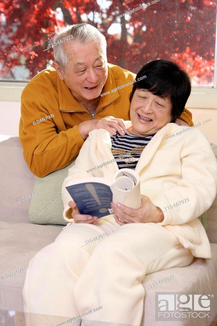 Stock Photo - Senior Asian man giving his wife a massage while she reads