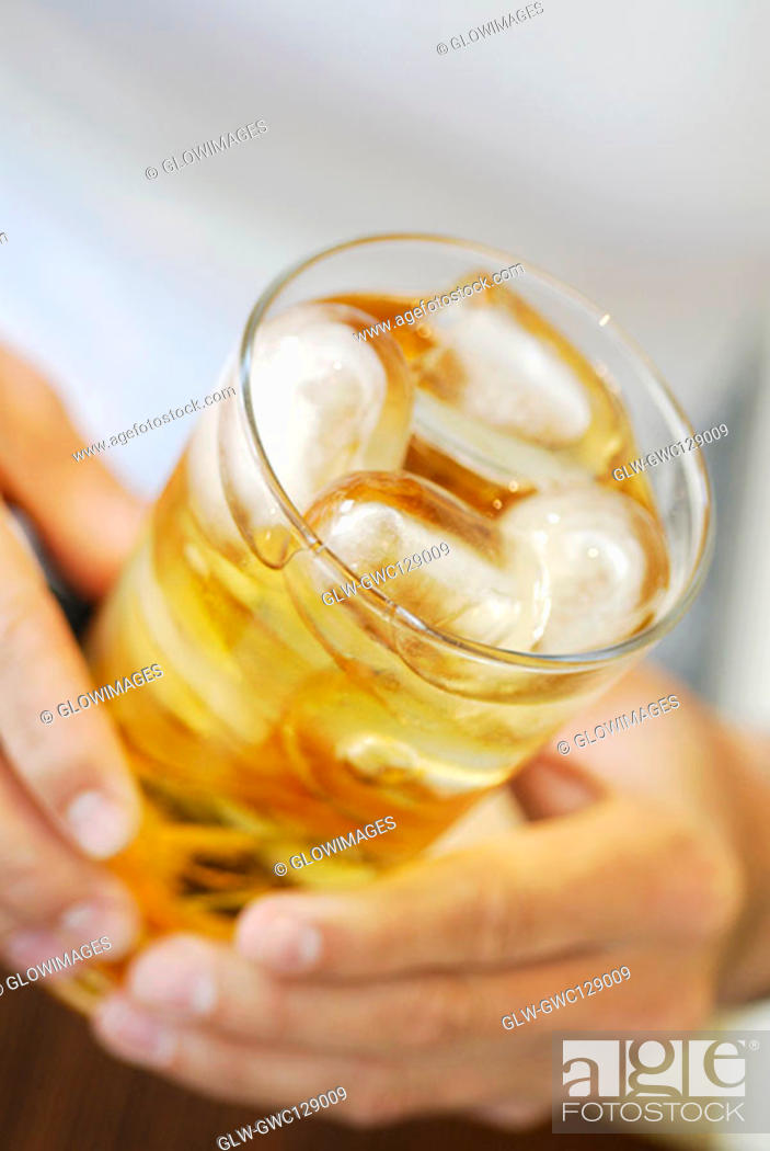 Stock Photo: Close-up of a person's hands holding a glass of lemonade with ice cubes.