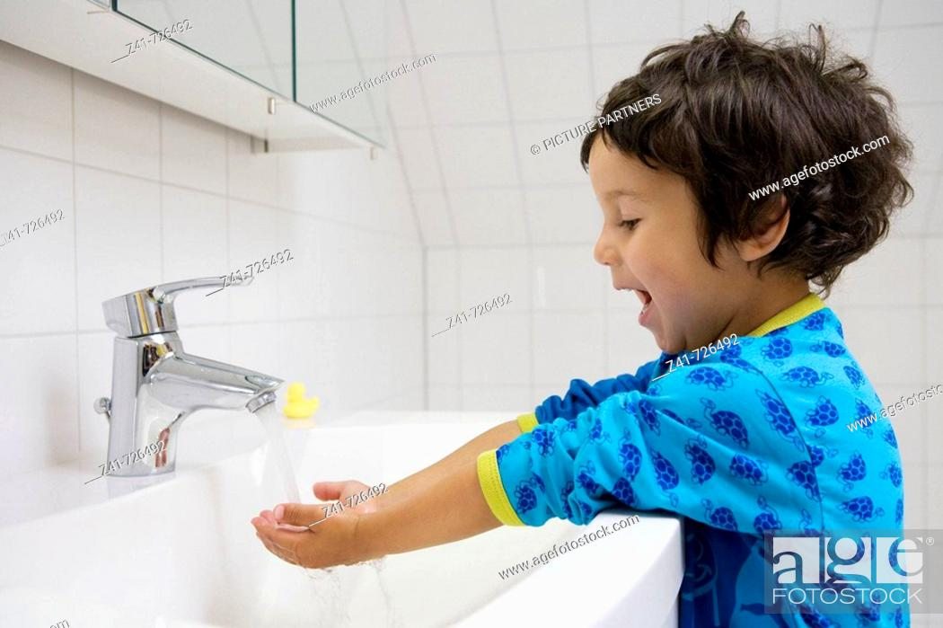 Stock Photo: Toddler washing his hands.