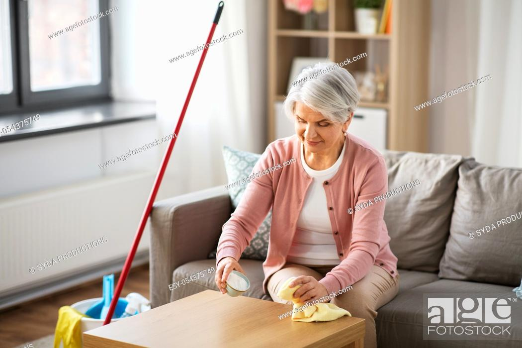 Stock Photo: senior woman cleaning table with soda at home.