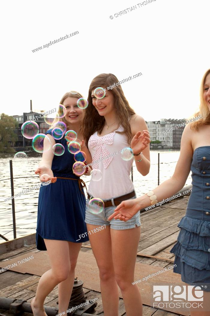 Stock Photo: Three female friends looking at bubbles on the Spree River, Berlin, Germany.