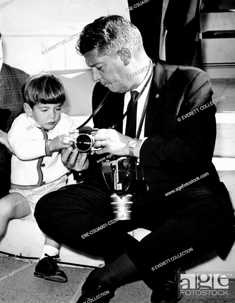 John F  Kennedy Jr  takes an interest in the cameras of