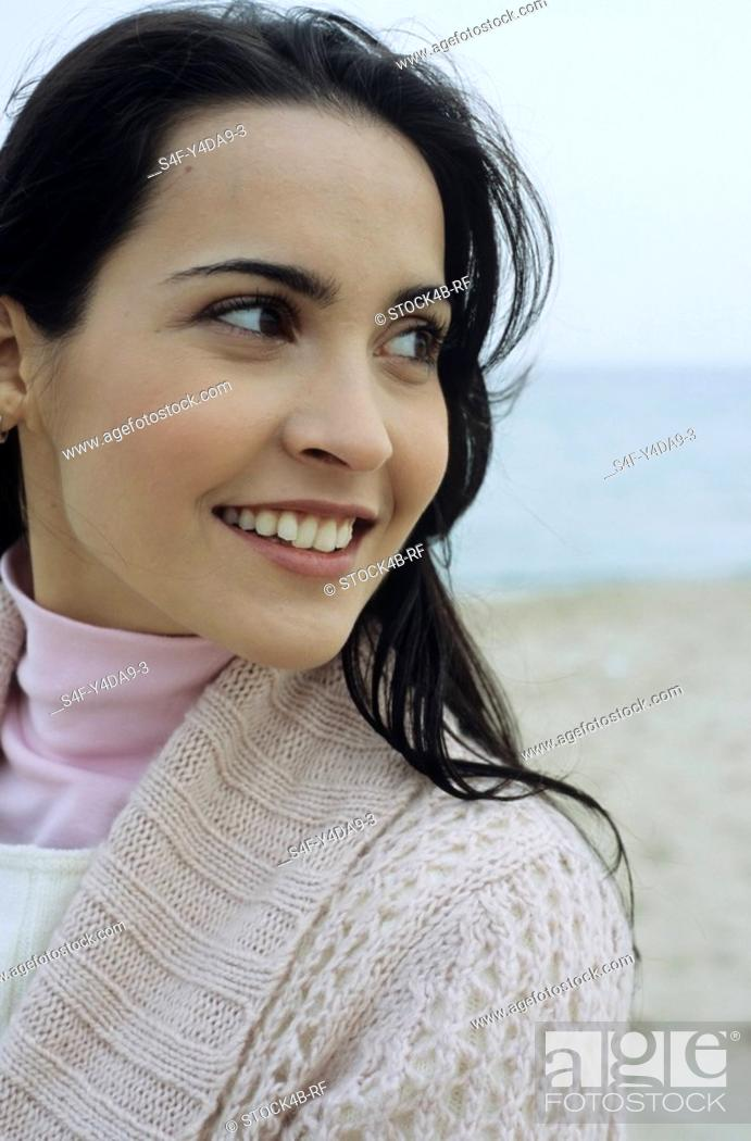 Stock Photo: Young brownhaired Woman with Cardigan at the Beach - Holiday - Temperature.