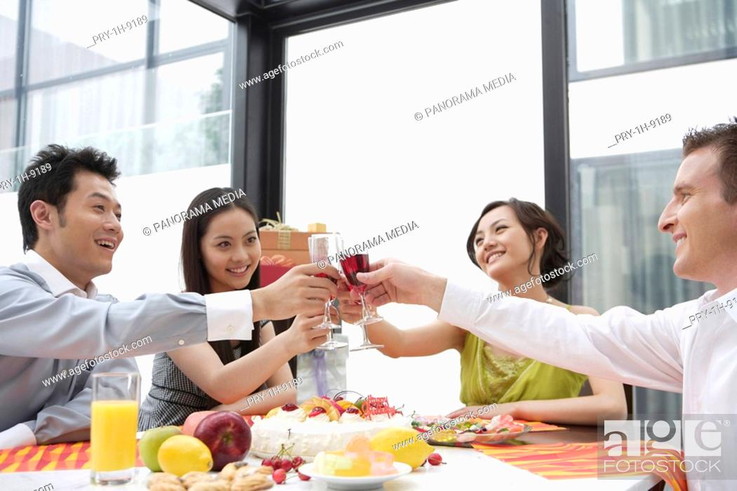 Stock Photo: Friends toasting wineglasses, smiling.