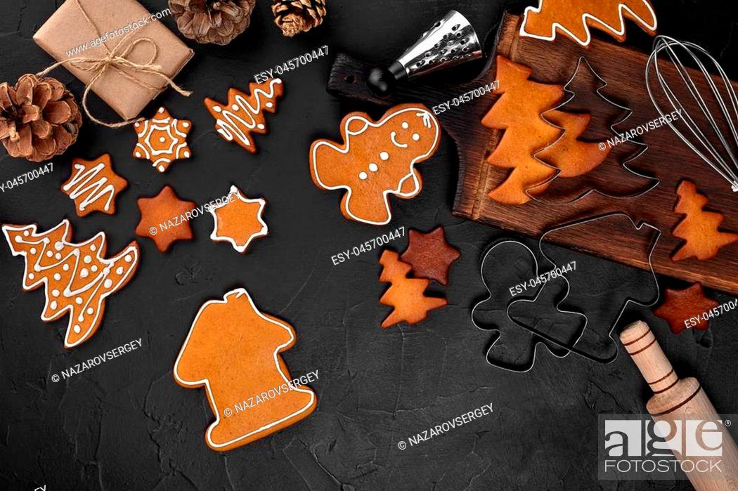 Stock Photo: Christmas homemade gingerbread cookies, spices and cutting board on dark background with copy space for text top view. Holiday, celebration and cooking concept.