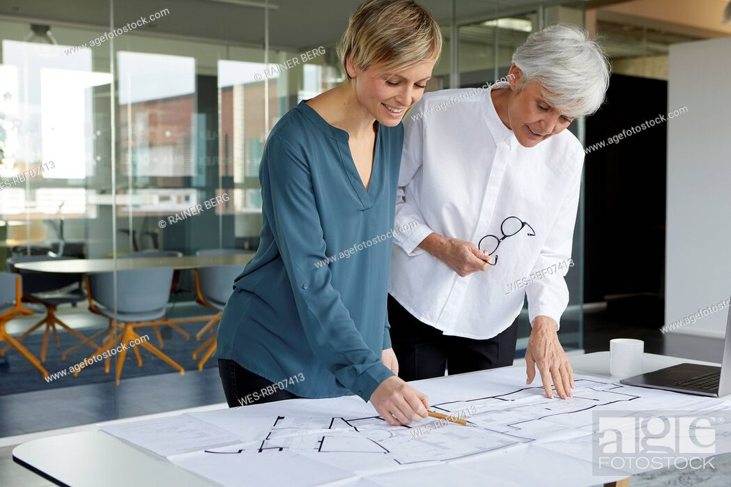 Stock Photo: Two businesswomen working together on construction plan in office.