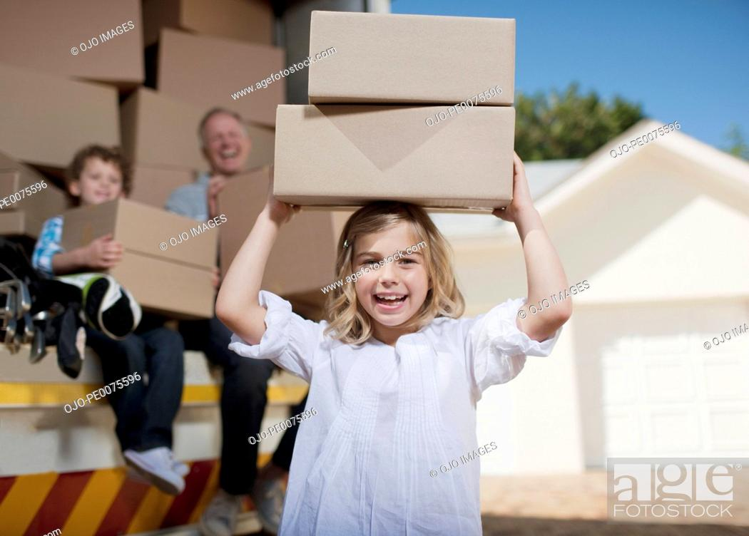 Stock Photo: Girl carrying boxes on her head from moving van.