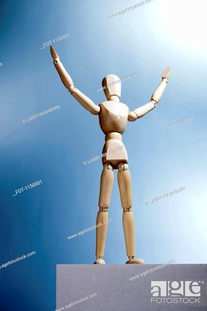 Stock Photo: An artist's figure standing atop a box with arms raised and head tilted up.