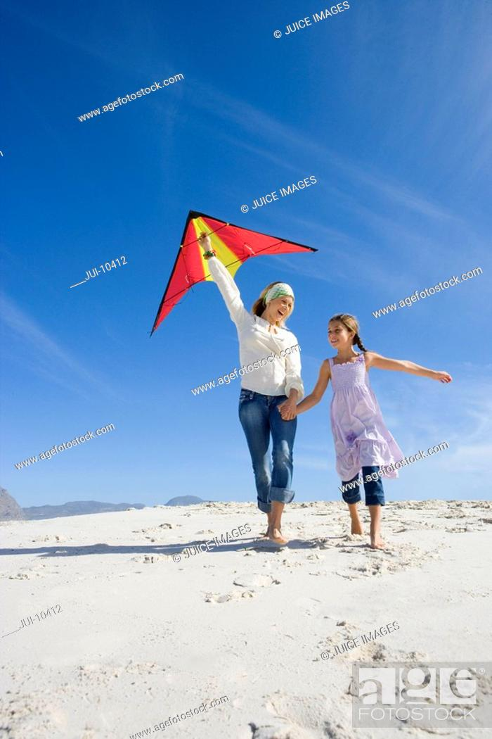 Stock Photo: Mother and daughter 5-7 with kite on beach, smiling, low angle view.