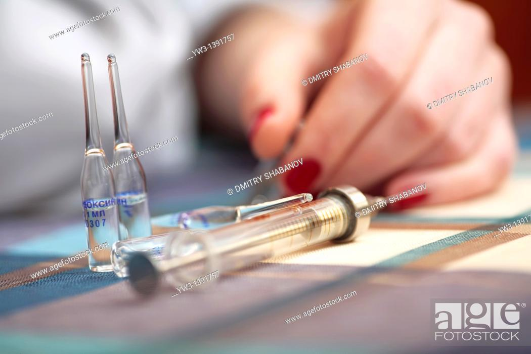 Stock Photo: women and drags syringe on the table.