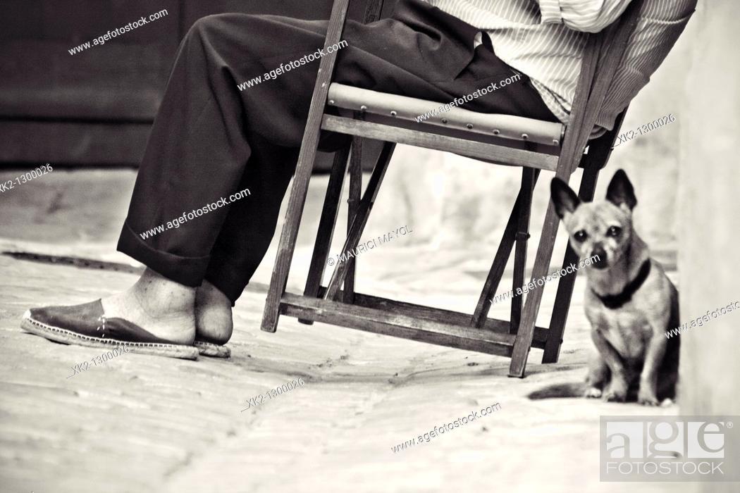 Stock Photo: Elderly man sitting on typical Minorca chair (aka. 'Coca Rossa') with dog. Ciutadella de Menorca, Minorca, Balearic Islands, Spain.