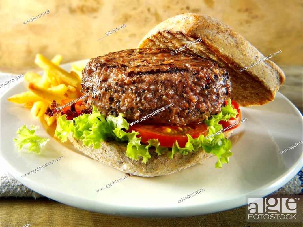 Stock Photo: Peppered beef burger with chips and wholemeal bun.