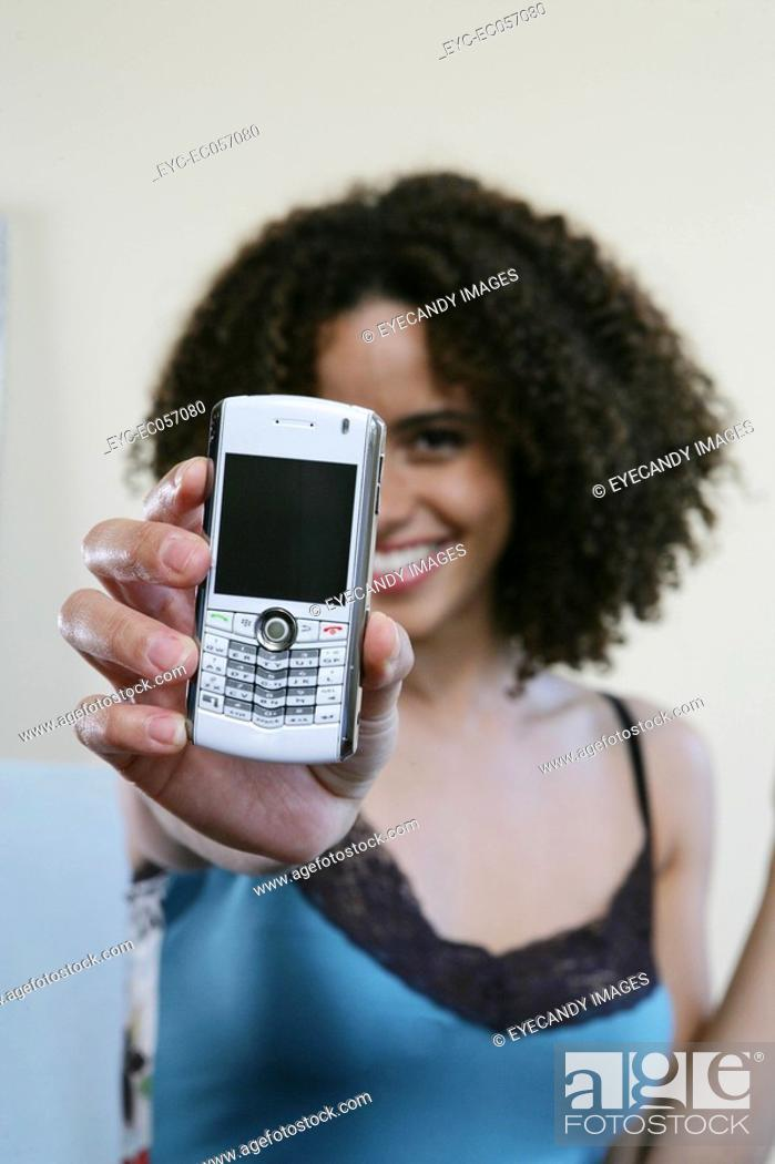 Stock Photo: Woman holding a cellphone/blackberry up to camera.