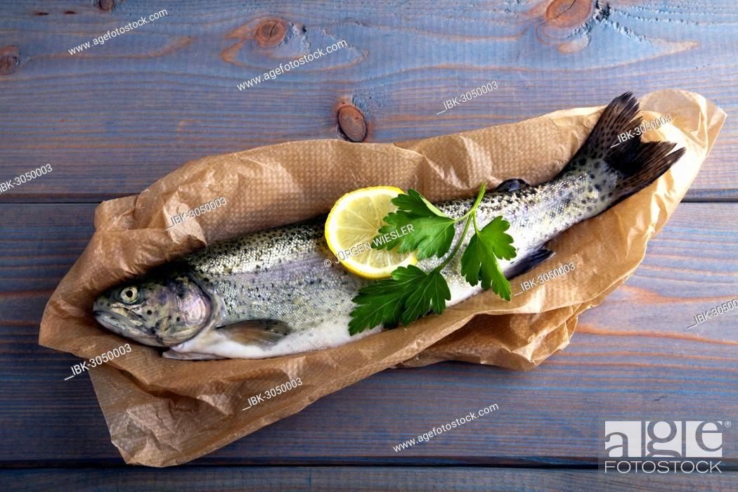 Stock Photo: Fresh brook trout in baking paper on a wooden surface.