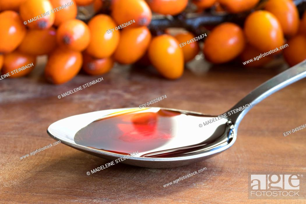 Stock Photo: Sea buckthorn oil on a spoon with sea buckthorn branches in the background.